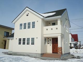 緑の屋根とアイボリー塗壁の南欧風住宅